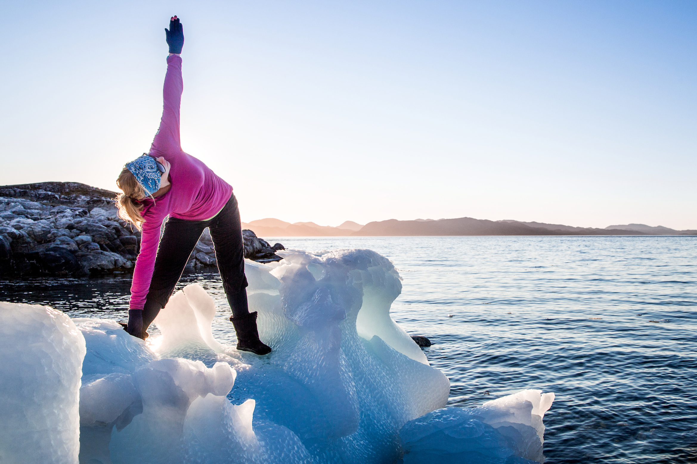 A meditative yoga moment at sunset on a stable beached iceberg in Nuuk